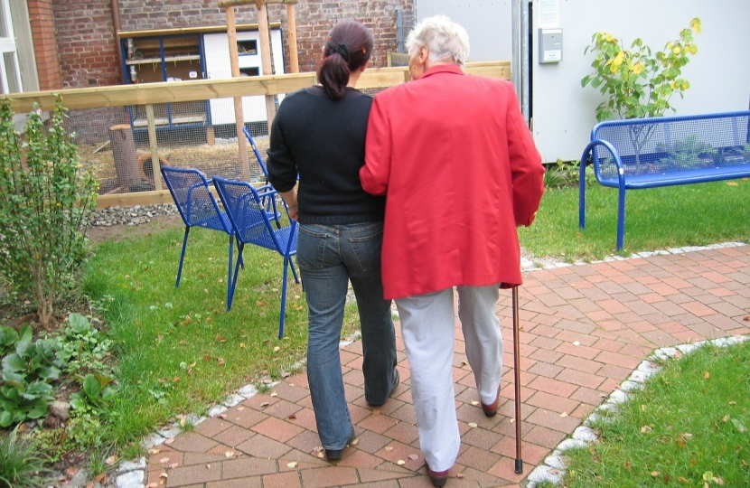 A resident of a care home with a carer.